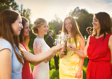 Bride with four happy bridesmaids toasting at the wedding reception outside photo