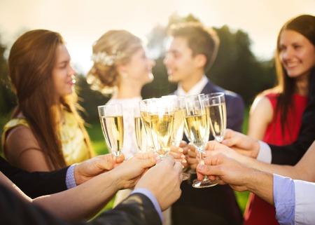 Invitados a la boda tintineando anteojos mientras los recién casados se abrazan en el fondo Foto de archivo