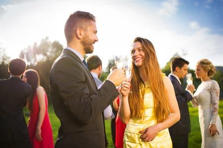 matrimonio feliz: Invitados a la boda que tintinean los vidrios en la recepci�n de la boda fuera Foto de archivo