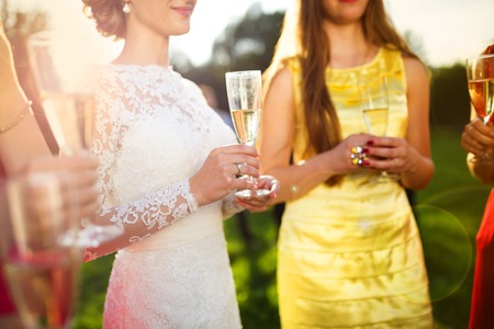 formal garden: Bride with four happy bridesmaids toasting at the wedding reception outside
