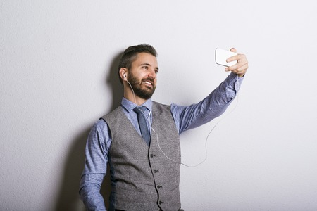 Studio shot of modern hipster businessman taking selfie with mobile phone photo