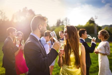 brindisi champagne: Gli invitati a nozze tintinnano bicchieri mentre i novelli sposi che beve champagne in background