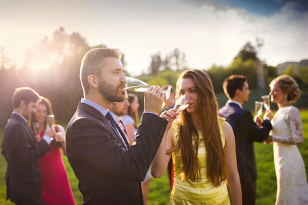 Wedding guests drinking champagne while the newlyweds clinking glasses in the background photo