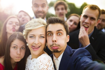 Young couple of newlyweds with group of their friends taking selfie and making funny grimaces