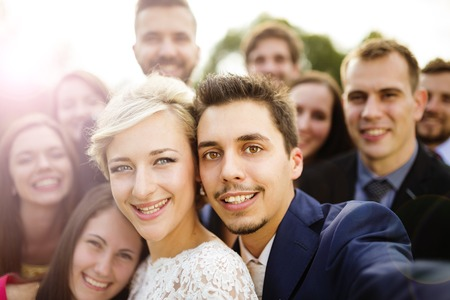 Young couple of newlyweds with group of their firends taking selfie photo