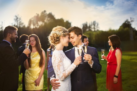 groom: Young newlyweds clinking glasses and enjoying romantic moment together at wedding reception outside