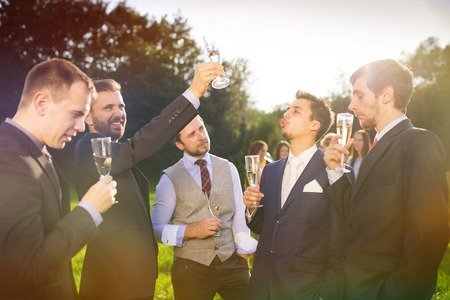 groom: Groom with four happy groomsmen toasting at the wedding reception outside
