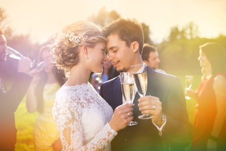 Young newlyweds clinking glasses and enjoying romantic moment together at wedding reception outside