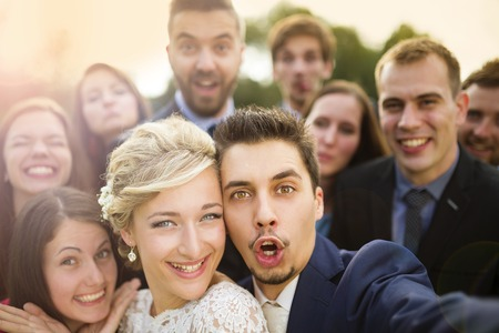marriages: Young couple of newlyweds with group of their firends taking selfie and making funny grimaces