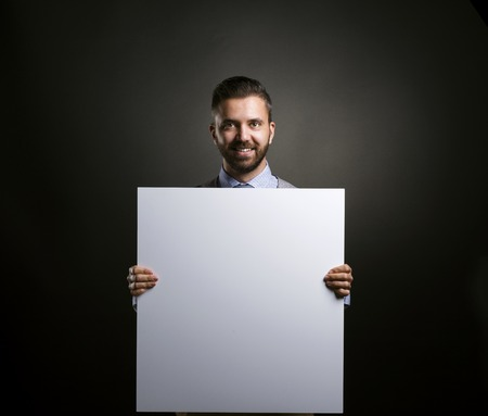 Studio shot of modern hipster businessman holding blank advertisement on black background photo