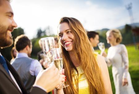 brindisi champagne: Ospiti di nozze tintinnano bicchieri al ricevimento di nozze di fuori