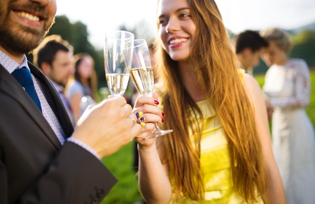 event: Wedding guests clinking glasses while the newlyweds hugging in the background
