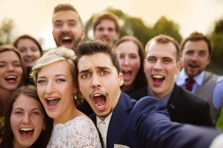 Selfie を取り、面白いしかめっ面を作る彼らの友人のグループと新婚の若いカップル