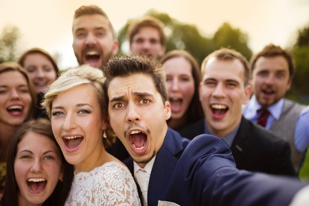 group picture: Young couple of newlyweds with group of their firends taking selfie and making funny grimaces