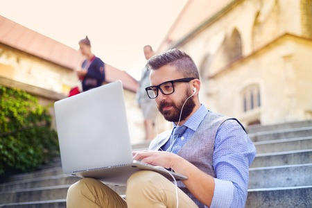 Handsome hipster modern businessman using laptop in the city photo