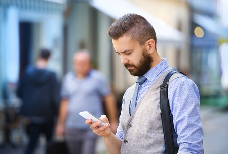 communication occupation: Handsome hipster modern businessman with beard walking in town with mobile phone Stock Photo