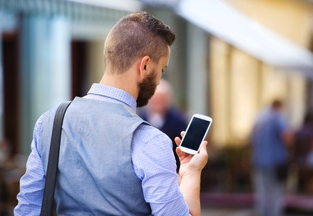 Handsome hipster modern businessman with beard walking in town with mobile phone photo