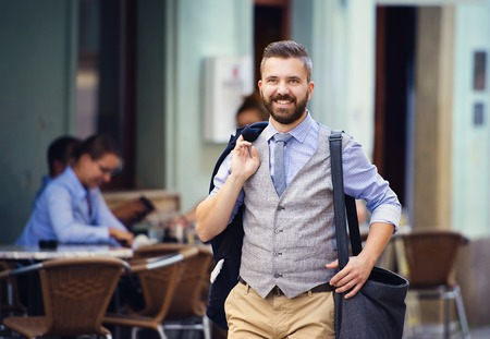 expert: Handsome hipster modern businessman with briefcase walking in town Stock Photo