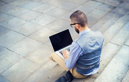 manos trabajo: Inconformista Apuesto hombre de negocios moderno usando la computadora port�til en la ciudad