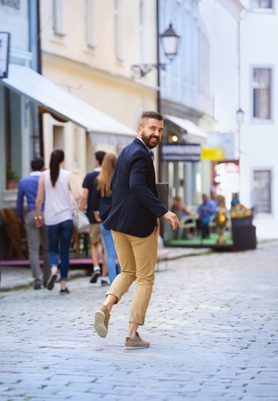 hurrying: Handsome modern hipster businessman with briefcase hurrying to work