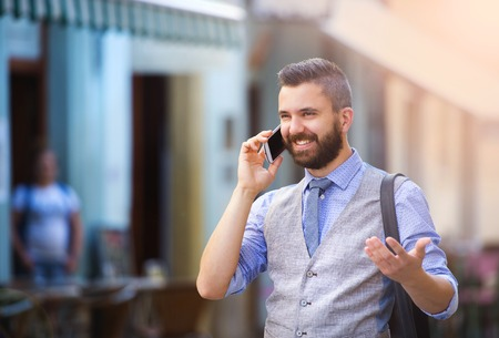 to phone calls: Handsome hipster modern businessman with beard walking in town and calling on mobile phone