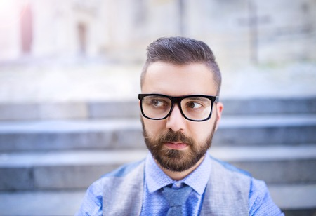 Handsome hipster modern businessman with beard and glasses in town photo