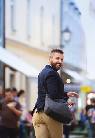 busy beard: Handsome modern hipster businessman with bag hurrying to work Stock Photo