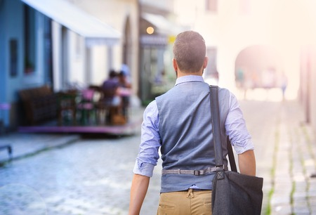 Handsome hipster modern businessman with briefcase walking in town Stock Photo