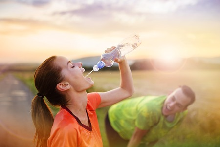 Cross-country trail running couple having water break at sunset