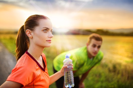 Cross-country trail running couple having water break at sunset photo