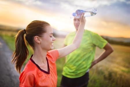 having a break: Cross-country trail running couple having water break at sunset
