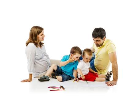 Portrait of the happy family with two children and pregnant mother drawing, isolated on white background photo