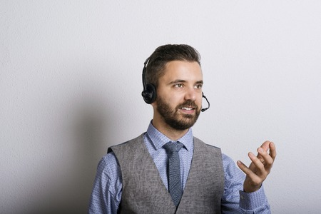 center agent: Call center operator isolated on white. Young handsome hipster man with headset.