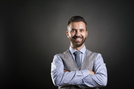busy beard: Studio shot of modern hipster businessman, isolated on black background