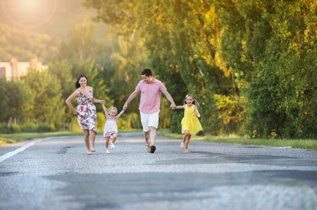an active: Familia feliz que se divierte durante la caminata en la carretera