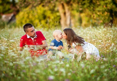 happy family nature: Happy family with little boy sitting on meadow in summer and eating homemade muffins Stock Photo