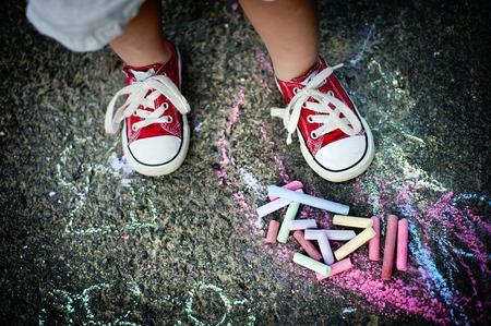 보도에 크레용으로 그리기 캔버스 신발에 어린 소년의 닫습니다