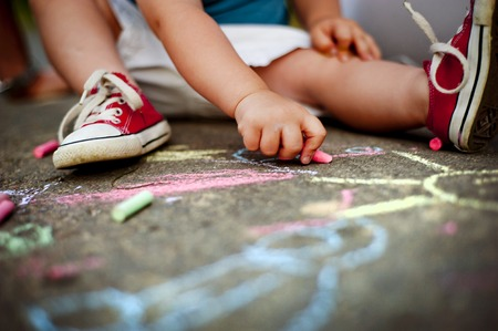 Close up of little boy in canvas shoes drawing with chalks on the sidewalk photo