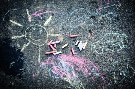 Childs drawing of sun and colorful chalks on a street photo