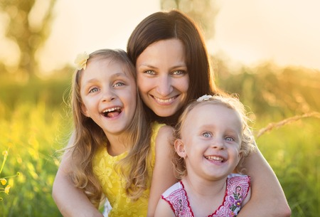 adult child: Portrait of young happy mother with her little daughters in sunny meadow