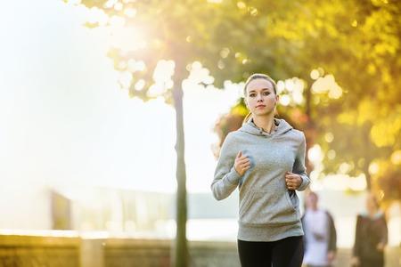 ジョギング若い女性ランナーにはマリーナの岸壁に都市で。スポーツ ライフ スタイル。