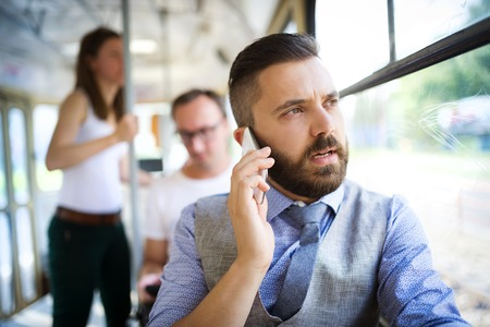 Handsome hipster modern man calling by mobile phone in tram photo