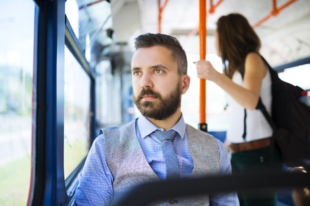 Handsome hipster modern man traveling by tram in town 版權商用圖片