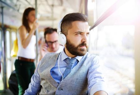 personas escuchando: Inconformista guapo hombre moderno con los auriculares que viajan en tranvía en la ciudad