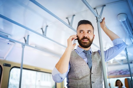 businessman waiting call: Handsome hipster modern man calling by mobile phone in tram Stock Photo
