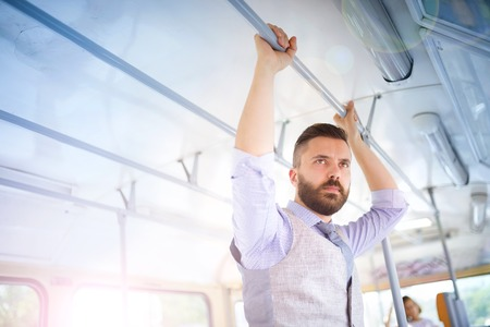 Handsome hipster modern man traveling by tram in town photo
