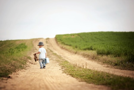 Rear view of little boy walking on the footpath in field with suitacase and teddy bear Фото со стока