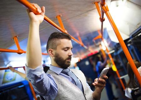 passenger buses: Apuesto hombre moderno inconformista llamando por teléfono móvil en el tranvía en la noche