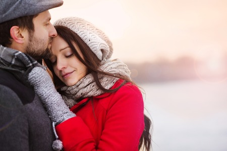 two girls hugging: Young couple hugging by the river in winter weather Stock Photo