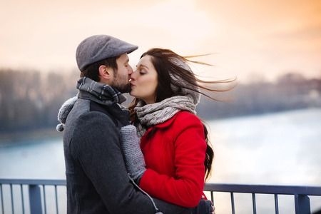 Young couple kissing by the river in winter weather Stockfoto
